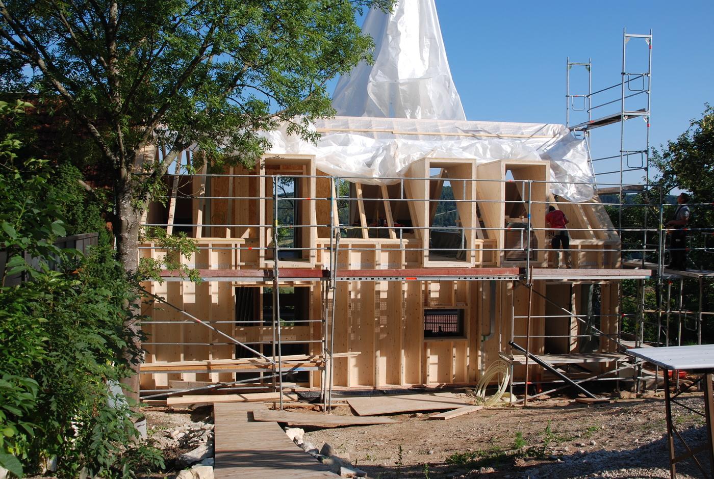 Holzhaus beim Bau mit Baugerüst