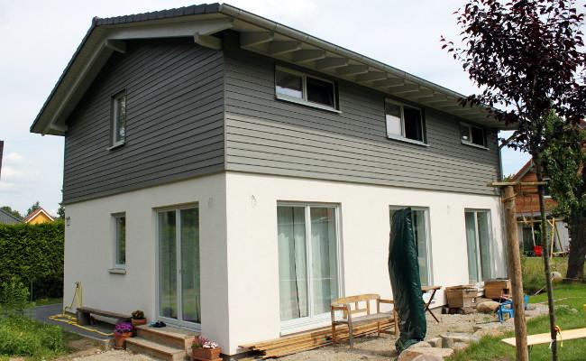 oberes Stockwerk mit grauer Holzverschalung, weißes Haus