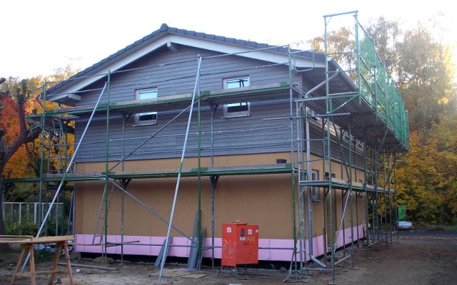 Baugerüst, dunkle Holzverschalung oberes Stockwerk