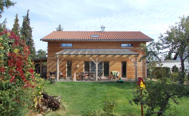 Holzhaus Rückseite mit blühendem Garten, Terasse