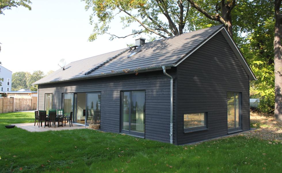 schwarzes Holzhaus, Rückansicht mit Terrasse