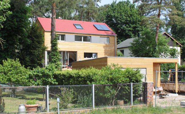 Holzhaus mit Garage, rotes Satteldach, Blick von Straße