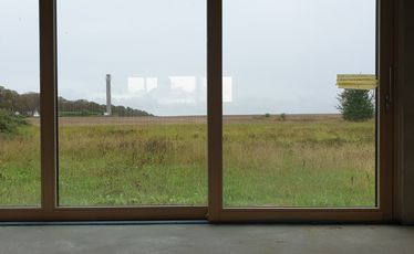 Blick durch Fensterfront nach draußen auf Grasland