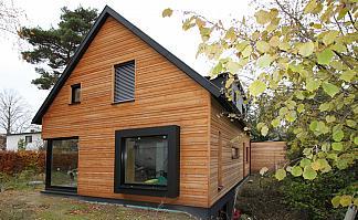Holzhaus mit schwarzer Fensterumrahmung hervorstehend, Dachüberstand,