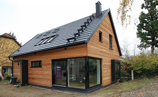 Holzhaus, Eingang und Wohnbereich von außen, Grundriss mit zentraler treppe, Schwarz eloxierte Metallelemente