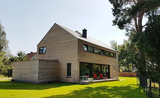Rückansicht mit Terrasse, schmale lange Fensterfront im Obergeschoss