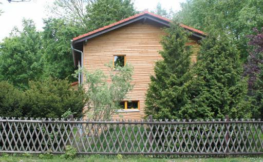 Haus, hervorstehendes Dach, Blick vom Zaun aus