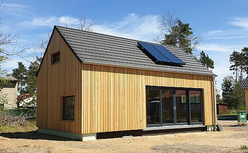 Holzhaus, große Glastüren, Solarpanele auf Dach